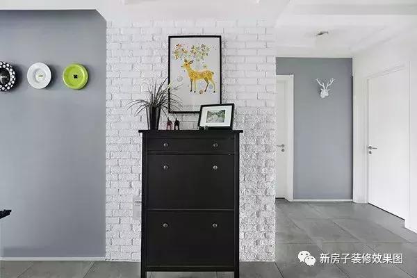 进门正面靠墙的鞋柜,纯黑色设计配上白色的文化石墙砖和彩色卡通装饰