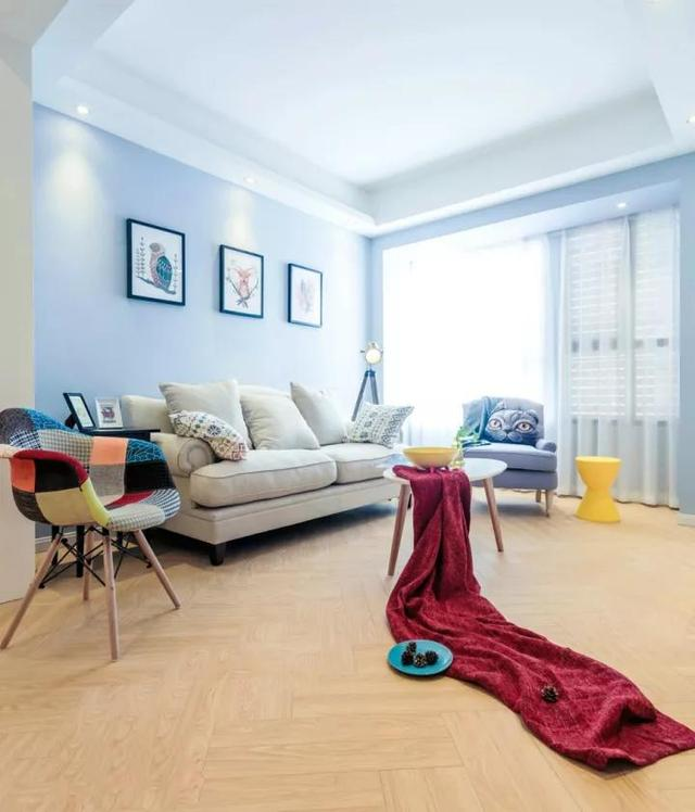 客厅以淡蓝色的乳胶漆刷新墙面,搭配原木质感的地板,还有舒适的布艺